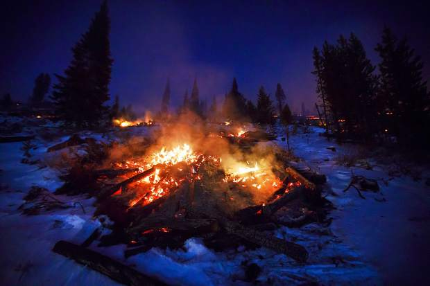 Slash piles continue to burn through the night along Swan Mountain Road on Nov. 7, near Frisco.