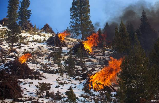 Slash piles burn along Swan Mountain Road Thursday, Nov. 15, near Frisco.