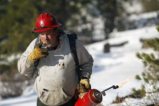 National Forest Service wildland firefighter Mike Ottosen walks between slash piles to burn along Swan Mountain Road Thursday, Nov. 15, near Frisco.