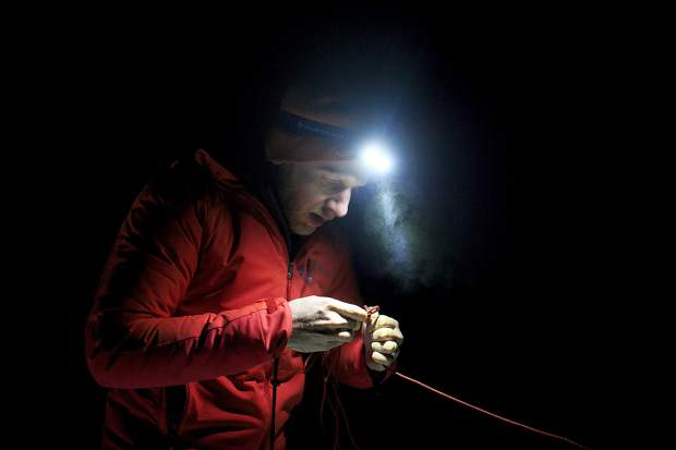 Matt Coye, a volunteer recruit for the Summit County Rescue Group, sets up a knot for shelter during survival training Thursday night, Nov. 8, on the Frisco Peninsula.