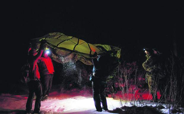 Volunteers for the Summit County Rescue Group practice using a parachute to cover themselves in a huddle position during survival training Thursday night, Nov. 8, on the Frisco Peninsula.