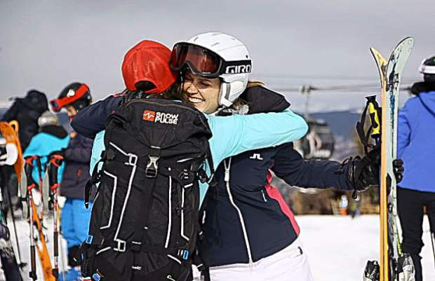 Friends hug each other at the top of Aspen Mountain for opening day on Saturday.