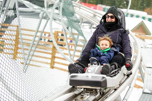 A mother and son take the alpine coaster down on Snowmass on opening day Thursday.