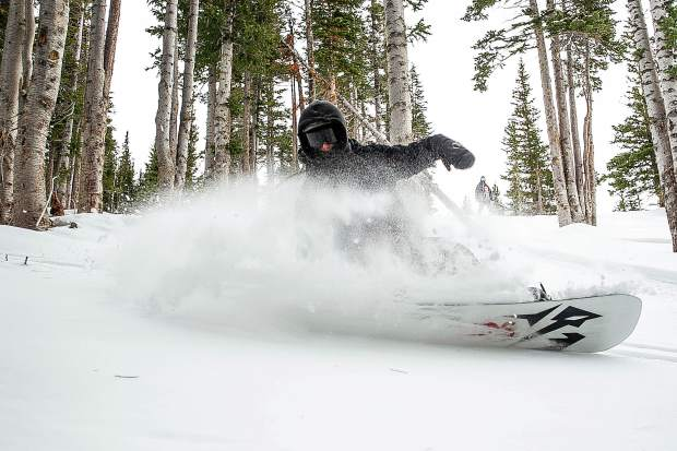 Ben Sydoryk slashes through some powder on Snowmass Mountain on opening day Thursday.