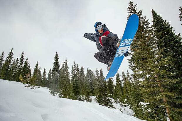 Josh Stump does a grab off of a jump on Snowmass Mountain on opening day Thursday.