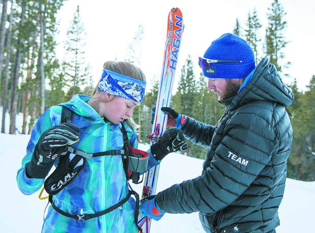Summit Endurance Academy coach Joe Howdyshell gives advice to cadet ski mountaineering athlete Jazlyn Smith on how to effectively hook the skis onto her backpack during skill-set practice on Tuesday, Dec. 11, in Breckenridge.