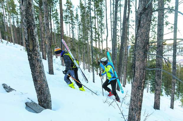 Ski mountaineering athletes Mark Jardim, left, and Finn Remias boot-pack uphill during practice on Tuesday, Dec. 11, in Breckenridge.
