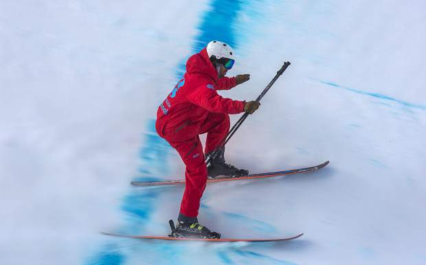 Grounds crew member scrapes lumps of snow off at the bottom of the halfpipe Friday, Dec. 7, at Copper Mountain.