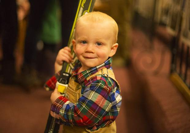 Tate Gibbs, 15 months, smiles for the camera holding his skis during the blessing Wednesday, Nov. 28, in Breckenridge.