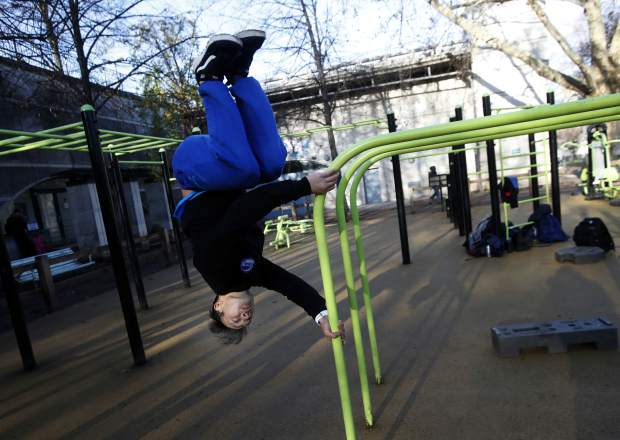 Parkour co-founder Chau Belle trains in a park in Paris, Thursday, Dec. 20, 2018. Belle was one of nine co-founders of the street sport born in the suburbs of Paris in the 1990s. Parkour is involved in a custody battle now with gymnastics, whose leaders are trying to take the sport under their wing. (AP Photo/Christophe Ena)
