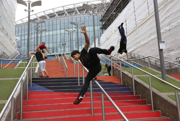In this Aug. 16, 2018, file photo, participants of the Parkour Generations work on their practice runs outside of Wembley Stadium ahead of the 13th Rendezvous International Parkour Gathering in London. The gymnastics federation has declared parkour to be its newest discipline and intends to lobby for its inclusion in the 2024 Olympic Games in Paris. This despite howls of complaint from parkour groups and a #WeAreNOTGymnastics protest movement by parkour lovers on social media. (AP Photo/Nishat Ahmed, File)