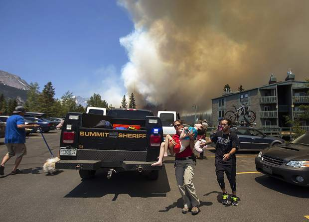 Residents, including one disabled boy, evacuate their homes with help from Summit County Sheriff Department's Erin Sirek as the wildland fire approaches in the Wildernest neighborhood Tuesday, June 12, near Silverthorne.
