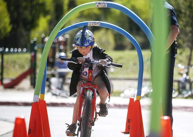 Upper Blue Elementary School student Keenan McMahon ducks and pedals through an obstacle course during the Bike Rodeo event Friday, June 1, on the school grounds in Breckenridge. The event educates kids on safety tips, traffic laws, and proper use of bicycle equipment hosted by the Red, White, and Blue Fire Department.