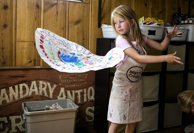 Breckenridge resident Ester Bailey, 6, flies her artwork, painted by oil pastels on a coffee filter canvas, during a summer camp session led by Breckenridge Creative Arts Tuesday, July 10, inside the Quandary Antiques Cabin.