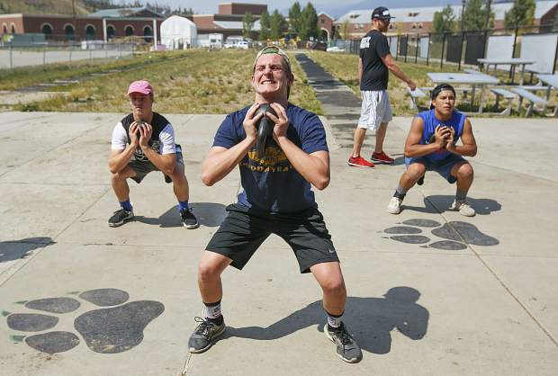 Summit High School football players from left, Camron Kalaf, Cyle Goff, and Alexi Urtusuasteguinelares do squat lifting with kettleballs during a team workout Monday, Aug. 20, at Climax Molybdenum Field at Tiger Stadium in Breckenridge.