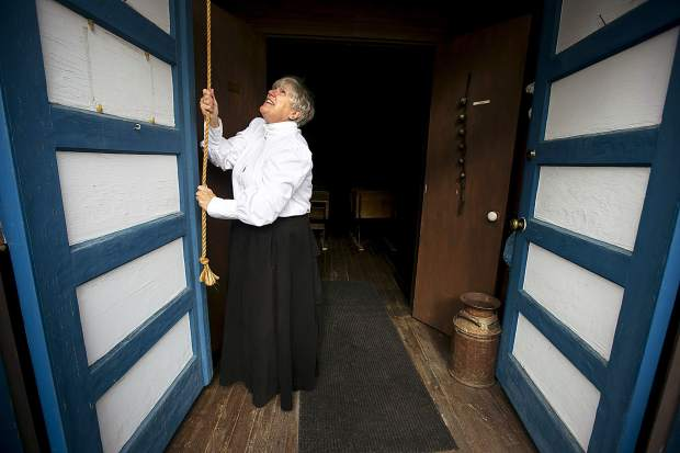 The Historical Society member Christy Nelson, impersonating as a schoolmarm, rings the first bell at the 1883 Schoolhouse Museum on the county-wide first day of school Wednesday, Aug. 22, in Dillon, CO.