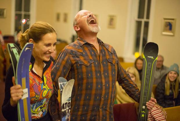 Carl Richter reacts after being splashed by the water during a blessing with Janet Ulrey and their skis Wednesday, Nov. 28, at St John's Episcopal Church in Breckenridge. Local residents gathered inside St. John the Baptist Episcopal Church in Breckenridge with their skis, snowboards, snowshoes and one snow shovel for the third annual blessing of winter gear.