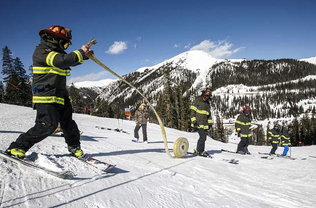 Red, White, and Blue Fire Department's team of five firefighters kick off their race by extending the fire hose to teammates before descending for the slalom gates in the 12th Annual Fire Hose Relay Race Friday, Feb. 23, at Arapahoe Basin Ski Area.