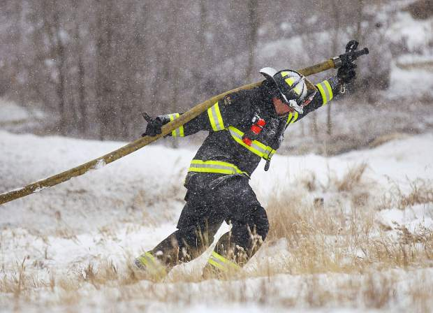 A firefighter from the Red, White & Blue Fire Department drags the hose to put out the fire at The Enclave condos Friday morning, Nov. 23, near Keystone Ski Resort. The fire was reported at 6 a.m. and no was was injured.