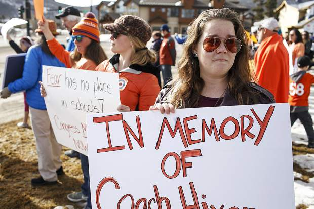 South Florida area high school graduate and current Breckenridge resident Becky Van Horn, 24, holds the sign remembering her late Coach Chris Hixon, who was killed in the shooting shooting in Parkland, Florida last month, during a National School Walkout Day protests Wednesday, March 14, along Main Street in Frisco, Colo. School students participated in a nationwide rally for 17-minutes, one minute for each student killed in the recent school shooting.