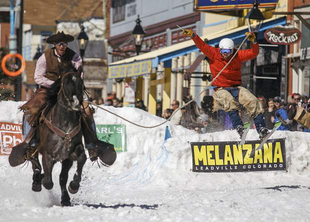 A horse and the rider pulls a skier off a jump during the 70th Annual Ski Joring competition Saturday, March 3, on Main Street in Leadville.