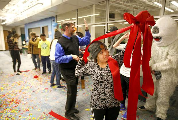 Snowy Peaks High School student Angelita Buller raises the bow used for the ribbon cutting ceremony Wednesday, Nov. 14, in Frisco. The school celebrated the second phase of the construction, which linked to the junior high program.