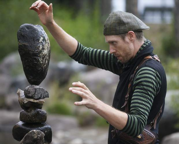 Artist Michael Grab carefully stack the rocks in Blue River in part of Breckenridge International Festival of the Arts Friday, Aug. 10, in Breckenridge.