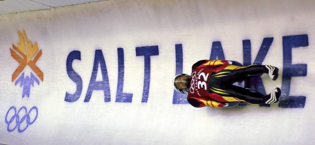 Georg Hackl, of Germany, speeds past an Olympic logo during a practice run for the men's singles luge at the 2002 Salt Lake City Winter Olympics in Park City, Utah.