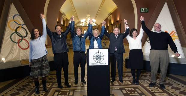 Salt Lake City Council Chairwoman Erin Mendenhall, Fraser Bullock, chief operating officer of the 2002 Winter Games, Jeff Robbins, president and CEO of the Utah Sports Commission, Salt Lake City Mayor Jackie Biskupski, Gov. Gary Herbert, USA Olympic speed skater Catherine Rainey-Norman and Salt Lake County Councilman Jim Bradley raise their arms in celebration after the USOC choose Salt Lake over Denver to bid on behalf of the U.S. for future Winter Game on Friday in Salt Lake City.