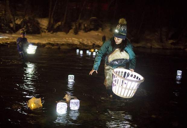 Volunteer Amy Lyndon picks up the lanterns in the Blue River following the Noche De Candela during First Friday, Feb. 1, in Silverthorne.