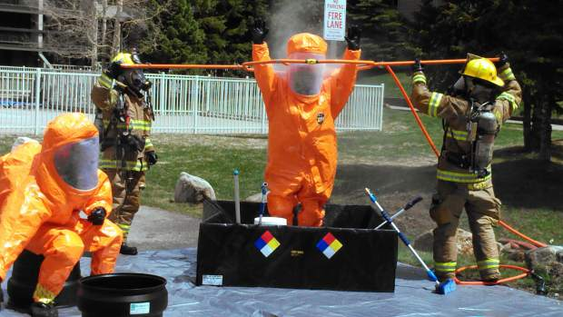 After containing a chlorine-gas leak in Keystone on May 22, 2013, firefighters in their protective gear had to be decontaminated after leaving the