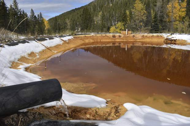 In this Oct. 12, 2018 photo, water contaminated with arsenic, lead and zinc flows from a pipe out of the Lee Mountain mine and into a holding pond near Rimini, Mont. The community is part of the Upper Tenmile Creek Superfund site, where dozens of abandoned mines have left water supplies polluted and residents must use bottled water. (AP Photo/Matthew Brown)
