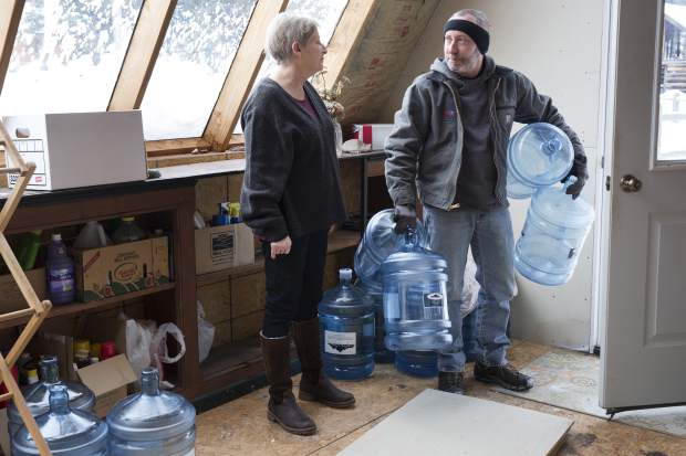 Catherine Maynard, a natural resource analyst for the U.S. Department of Agriculture, receives a bottled water delivery at her home in Rimini, Mont., by Bart Young of Big Spring Water on Feb. 18, 2019. About 30 households can't drink their tap water because groundwater was polluted by about 150 abandoned gold, lead and copper mines that operated from the 1870s until 1953. (AP Photo/Janie Osborne)