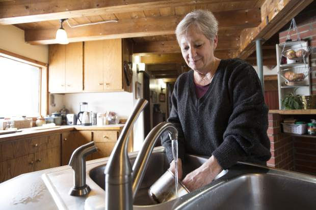 "Catherine Maynard, a natural resource analyst for the U.S. Department of Agriculture, washes dishes in her home in Rimini, Mont., on Feb. 18, 2019. ""The fact that bottled water is provided is great. ... Where it falls short is it's not piped into our home. Water that's piped into our home is still contaminated water. Washing dishes and bathing _ that metal-laden water is still running through our pipes,"" she says.  (AP Photo/Janie Osborne)"