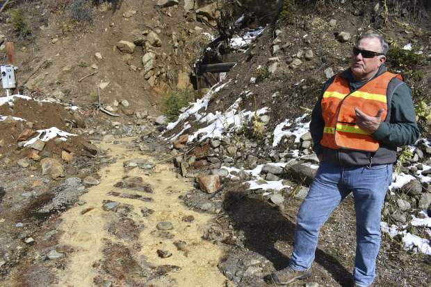 In this Oct. 12, 2018 photo, Tillman McAdams with the U.S. Environmental Protection Agency speaks about cleanup work at the Susie mine in Rimini, Mont., as polluted water from the mine flows near his feet. The mine is one of dozens that have fouled water supplies in the mountain community. (AP Photo/Matthew Brown)