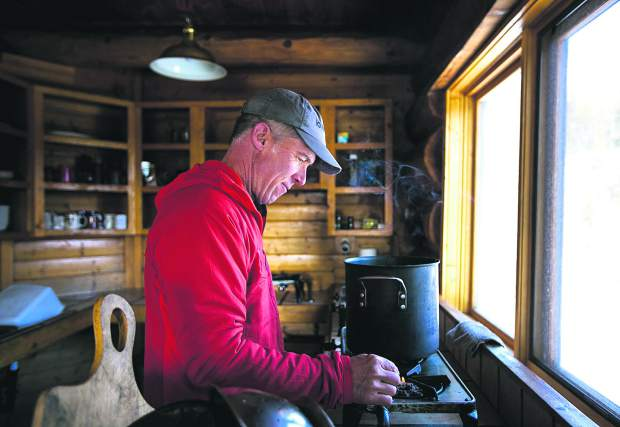 Summit Huts Association hutmaster Steve Huyler lights a match to heat the water on a stove for cleaning at Francie's Cabin on Tuesday, Feb. 5, near Blue River.