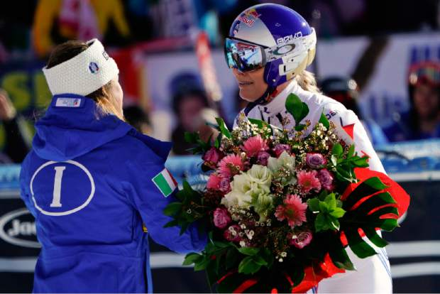 Lindsey Vonn, right, receives a bunch of flowers from Italy's Sofia Goggia after completing an alpine ski women's World Cup super-G event in Cortina D'Ampezzo, Italy on Sunday.