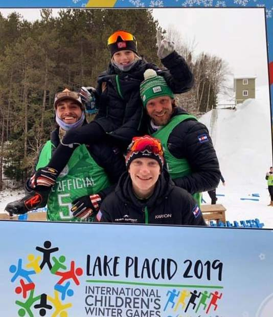 A collection of Team Frisco athletes and coaches pose for a photo with the International Children's Games sign earlier this week in Lake Placid, New York.