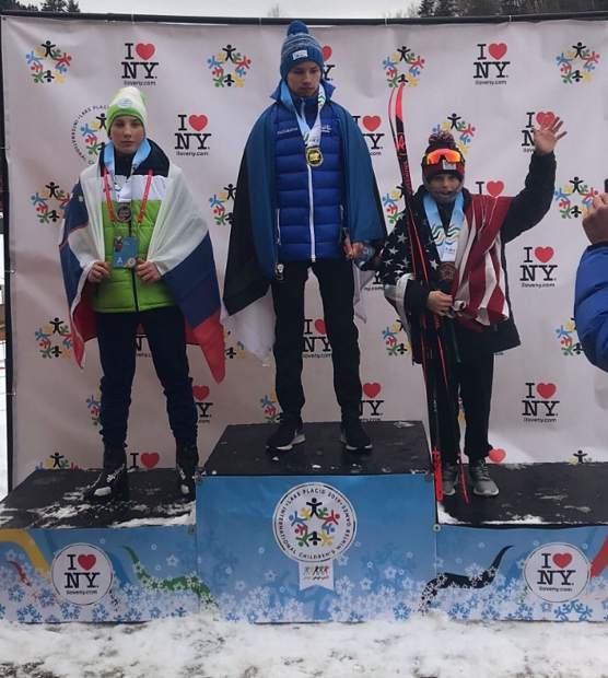 Team Frisco and Summit Nordic Ski Club skier Nico Konecny, right, wears the American flag after winning bronze at the International Children's Games in Lake Placid.