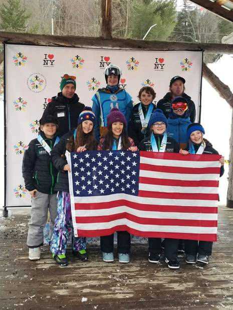 Members of the Team Frisco International Children's Games contingent comprised of Summit Nordic Ski Club and Team Summit coaches and athletes pose for a photograph on a podium on Tuesday in Lake Placid, New York.
