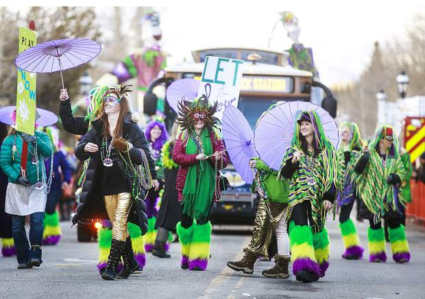 People dressed in boas, beads, and makes in the Mardi Gras Parade on Main Street Tuesday, Feb. 13, in Breckenridge.