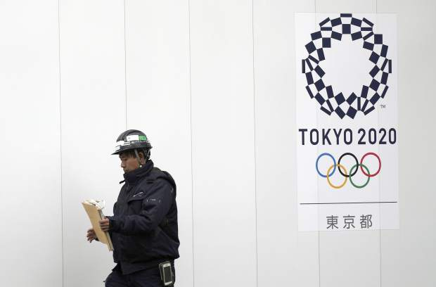 In this Feb. 12, 2019, photo, a worker walks past one of construction sites for the Tokyo 2020 Olympics in Tokyo. The price of the opening and closing ceremony for the Tokyo Olympics has risen about 40 percent according to numbers released by the organizing committee. (AP Photo/Eugene Hoshiko)
