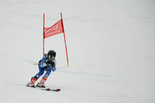 A Summit High School Alpine skier tucks her poles on a turn around a gate during Thursday's Colorado High School Ski League state-championship giant slalom competition at Purgatory Resort in Durango.