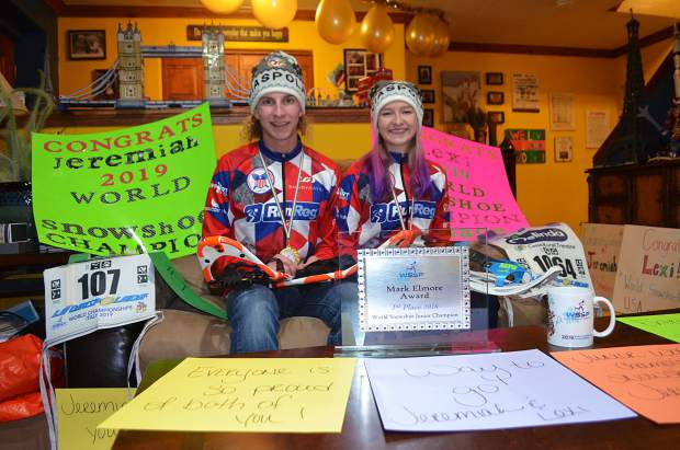 Siblings Jeremiah and Lexi Vaille (right) pose for a photograph with their World Snowshoe Championships gear, memorabilia and awards, along with all of the signs and decorations that their Aunt Sarah adorned their living room with to congratulate them on their performances, on Thursday evening.