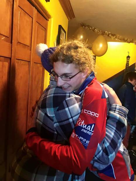 Jeremiah Vaille hugs a family member after returning home from his junior division victory at the World Snowshoe Championships in Fondo, Italy.