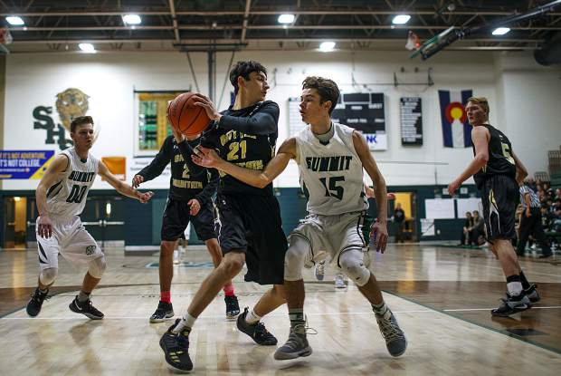 Summit High School senior guard Brendan Collins attempts to steal the ball from Battle Mountain High School senior guard Fernando Reyes during the Tigers' 72-50 home loss on Friday, Feb. 1, in Breckenridge.