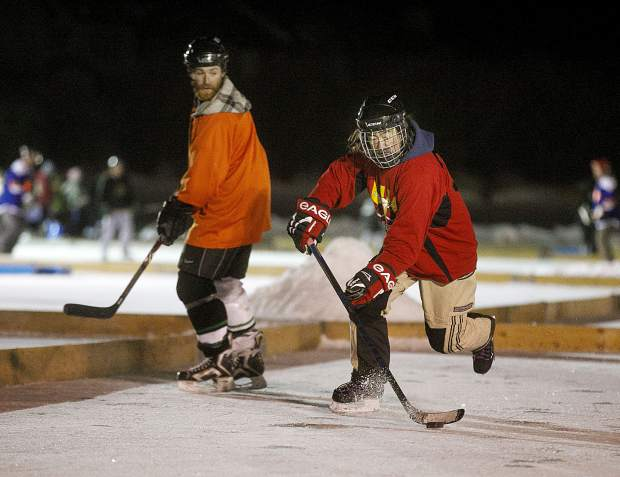 Three-player hockey teams teams attempt to gain control of the puck during the Pabst Colorado Pond Hockey Tournament on Friday, Feb. 15, at North Pond Park in Silverthorne.