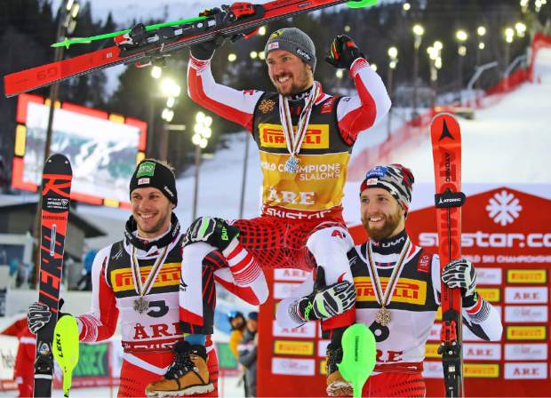 Austria's Marcel Hirscher, center, winner of the men's slalom, celebrates with second-placed compatriot Michael Matt, left, and third-placed compatriot Marco Schwarz, at the alpine ski World Championships in Are, Sweden, Sunday, Feb. 17, 2019. (AP Photo/Marco Trovati)