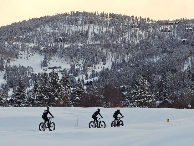 Cyclists pedal through the snow during Saturday's Ullr Bike race at the Gold Run Nordic Center in Breckenridge.
