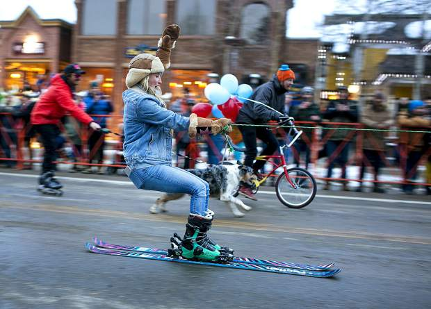 The 56th Ullr Fest Parade participant Kellyn Wilson zoom past others on skis with help of a vehicle Thursday, Jan. 10, on Main Street in Breckenridge.